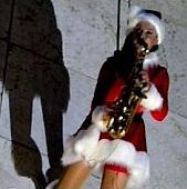 Saxophonkünstlerin Ines Weber läuft als Weihnachtsfrau an einer Hausfassade herab