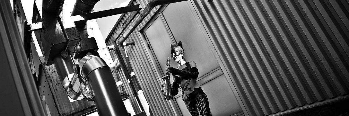 """Die """"Superheldin"""" im Catwoman-Kostüm spielt Saxophon auf einem Firmengebäude"""