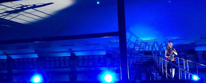 Saxophonkünstlerin spielt blau beleuchtet hoch oben im Wasserwerk