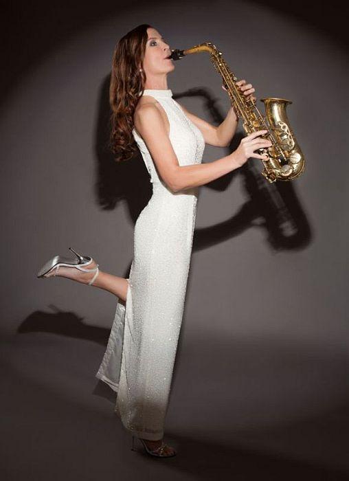 Saxophonistin Ines Weber in weißem Kleid mit Saxophon