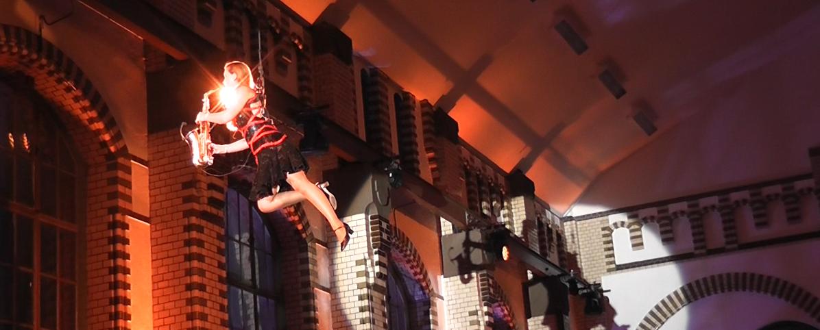 Saxophonkünstlerin Ines Weber seilt sich in einem Indoor-Event von der Decke herab