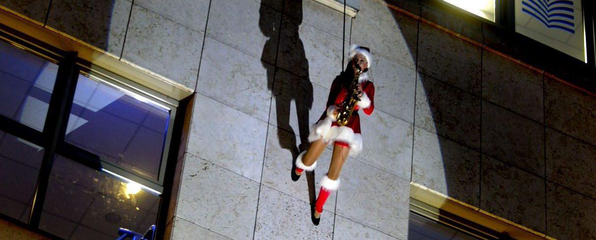 Ines Weber läuft als Weihnachtsfrau am Verticalsaxophon an einer Hausfassade herunter