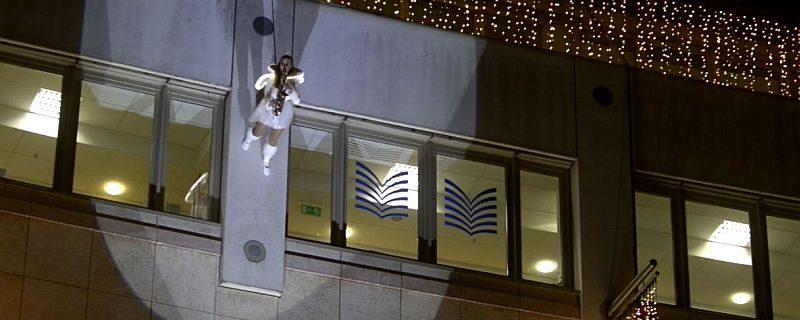 Saxophon spielend läuft Ines Weber im Kostüm eines Weihnachtsengels eine Fassade herab