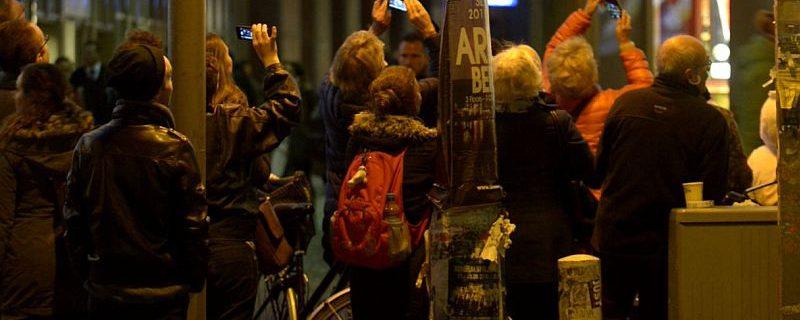 Zuschauer filmen das Herabschweben des artistischen Engels mit dem Saxophon