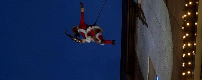 Als Weihnachtsfrau kostümiert spielt Ines Weber Verticalsaxophon während sie sich an den Allee Arcaden abseilt