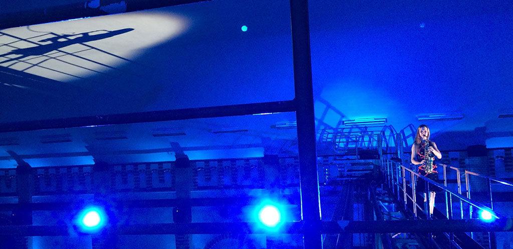 Künstlerin Ines Weber spielt Saxophon umgeben von blauem Licht - Indoor-ShowAct