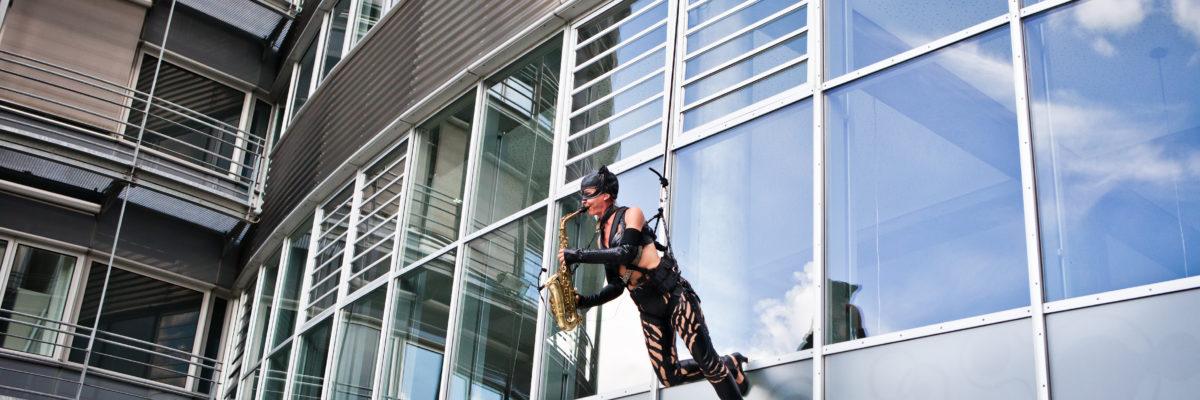 Ines Weber läuft als Catwoman die Fasssade von Air Liquide herab und spielt dabei Saxophon